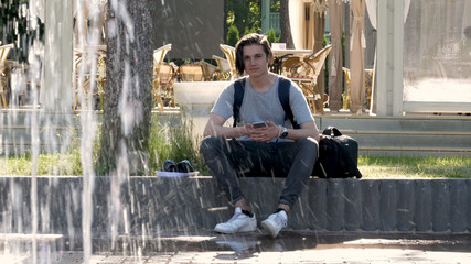 A young handsome guy (man) sits next to a fountain, writes a message on a mobile phone. Concept: young teenagers, lifestyle, schoolchild, student, park, summer.