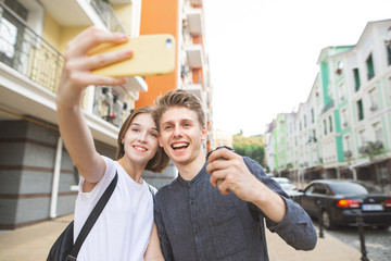 Happy smiling young couple posing at the camera and takes selfie smartphone. She takes selfie with a young man on the streets of the town. Happy together. Selfie concept. Love story
