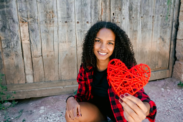 Beautiful young woman holding a red heart