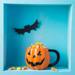 Halloween holiday composition with jack o lantern cup and candy corn
