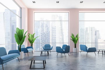 Pink wall office lounge area, blue sofas