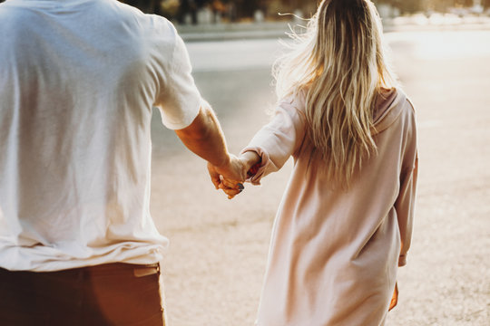 Crop couple holding hands on street