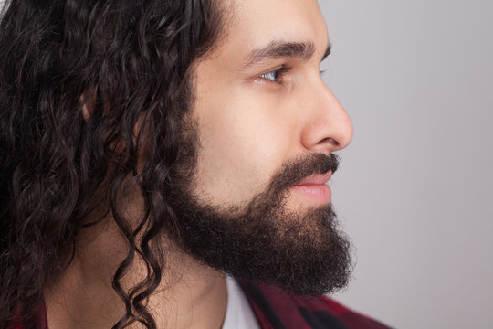 Closeup profile side view of handsome confident man with black long curly hair and beard, looking away with smile.indoor studio shot, isolated on gray background.