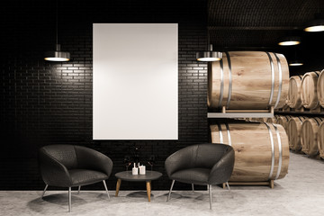 Black brick wine cellar, armchairs and poster