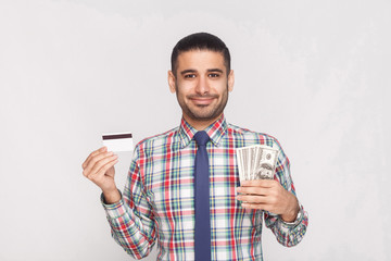 Banking savings. Joyful handsome young adult businessman in colorful checkered shirt with blue tie standing and holding fan of dollars and credit card. Indoor, studio shot, isolated on grey background