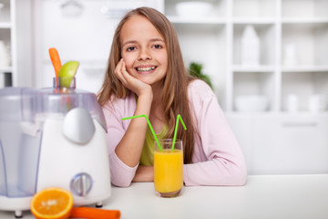 Happy teenager girl sitting in the kitchen with a fresh squeezed fruit juice
