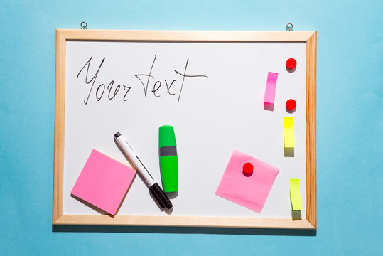 White board with marker pen and scratch paper isolated on blue paper background, top view with copy space