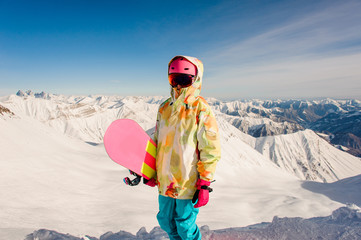 Female snowboarder in bright sportswear standing on the mountain top in Georgia, Gudauri