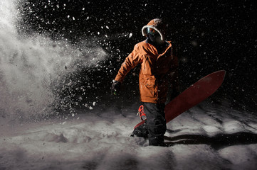 Professional snowboarder in orange sportswear with a board at night