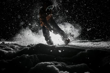 Active snowboarder in sportswear jumping on the board at night