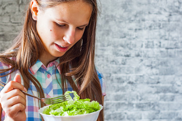 portrait of young teenager brunette girl with long hair eating green salad on gray wall background
