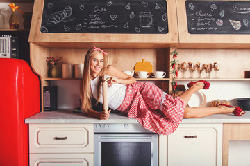 Pretty blonde long hair woman laying on the table, smiling and holding dough trolley in the red loft comfortable kitchen