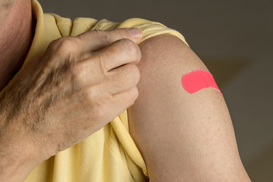 Senior man holding up shirt after flu injection