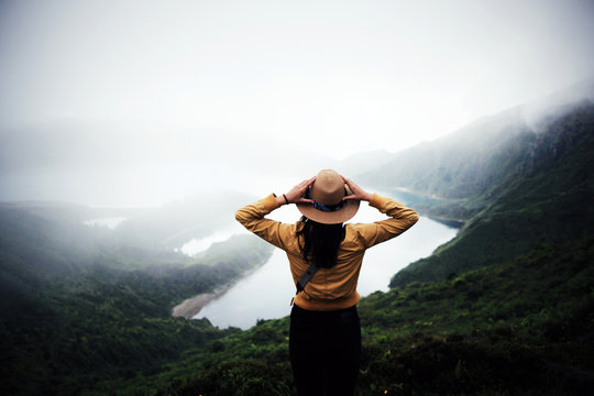woman traveler holding hat and looking at amazing mountains and forest, wanderlust travel concept, space for text, atmospheric epic moment, azores ,portuhal, ponta delgada, sao miguel