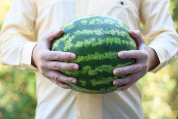 a man holding a large ripe watermelon