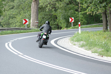 The man is riding on a motorcycle. He is dressed in a motorcycle outfit. You can see the speed of the ride. We see the driver from the back. Curve.