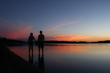 A romantic couple on a lake at sunset