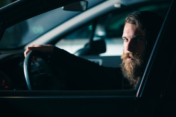 Man with beard and long hair in a car
