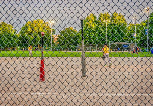 Unidentifiable youth league baseball players on diamond early evening baseball game, chain link fence in focus, background blurred, concept, copy space.