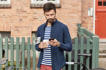 Outdoor shot of bearded concentrated man connected to smart phone internet for blogging via app, dressed in stylish clothing, carries newspaper, drinks takeaway coffee, stands near fence near building