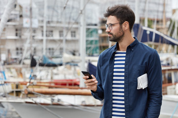 Horizontal view of thoughtful freelancer blogs in social networks, holds contemporary mobile phone, wears transparent glasses, poses against harbour background with copy space for your promotion