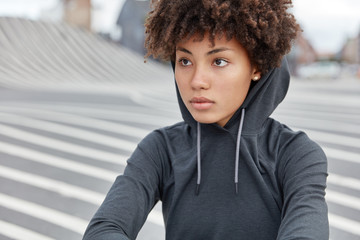 Cropped view of thoughtful dark skinned young sportswoman in stylish hoodie, focused into distance, sits on road against blurred background, has healthy skin. Ethnicity and lifestyle concept