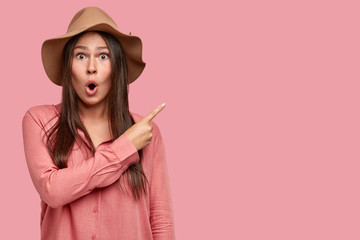 Surprised brunette Caucasian woman with astonished expression, keeps mouth opened from wonder, shows with index finger at blank space, advertises unusual item, isolated over pink background.