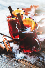Glass mugs of mulled wine with spices and citrus fruits on wooden table with autumn leaves and snow.