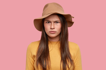 Portrait of dissatisfied woman has sad unhappy discontent expression, freckled skin, feels unhappy after ruined date, looks from under forehead, has sullen face, isolated over pink background