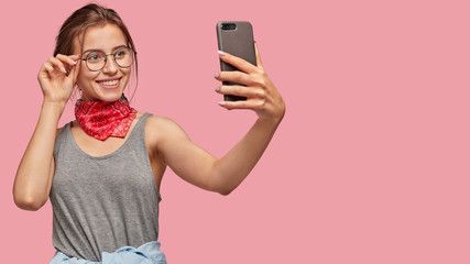 Glad satisfied woman with toothy smile, poses in front of cell phone camera, makes picture to upload at social networks, takes selfie, dressed in casual vest, isolated over pink studio wall.