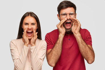 Photo of stressful European woman and man exclaim loudly, keep mouthes widely opened, yell with anger at somebody, stand next to each other, isolated over white background. Omg, its terrible