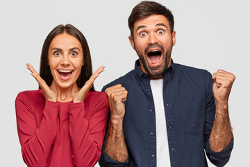 Amazed beautiful brunette young woman keeps hands near cheeks, exclaims with happiness, overjoyed bearded guy clenches fists, celebrate together their success, isolated over white background