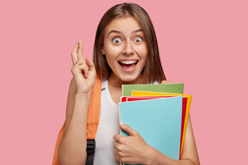 Photo of cheerful brunette woman with overjoyed look keeps fingers crossed, believes in everything good, holds books, has positive expression, poses against pink background. Body language concept