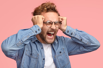 Sideways shot of desprerate stressful guy keep fists on temples, screams angrily, frowns in discontent, expresses negative feelings, dressed in denim jacket, has beard and curly hair, models indoor