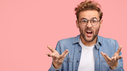Annoyed young Caucasian guy gestures with hands angrily, opens mouth and frowns face in discontent, poses against pink background with copy space for your advertisement or promotion, asks what to do