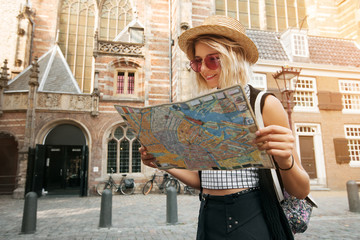 Traveler girl hold and look map in Amsterdam. Hipster tourist searching right direction on map, lifestyle concept adventure
