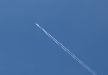 Plane flying on a blue sky, condensation line.