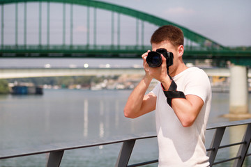 Professional photographer examining scenery and taking pictures of environment, architecture, urban elements, river, old green bridge. Tourist and traveler is making landscape photography with camera.