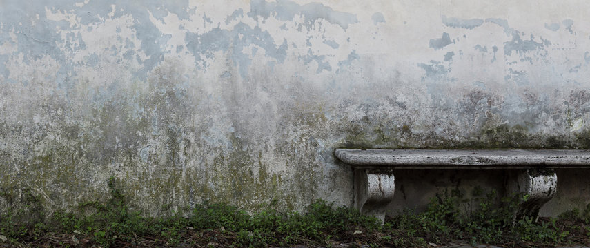 Ancient stone bench in front of old gray wall with crumbling plaster and green moss. Narrow vintage background