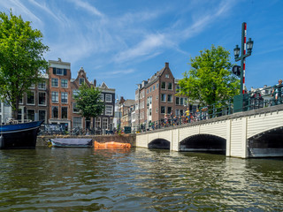 Buildings and boats along Amsterdam's beautiful  canals in central Amsterdam during the day. The canals are one of Amsterdam's main attractions.