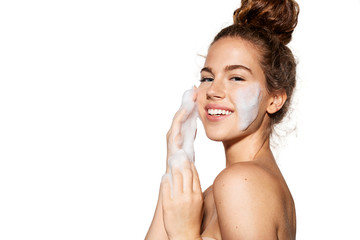 Portrait of young pretty girl with healthy skin on white background. Woman smiling and applying cosmetic foam on face.  Beauty skincare concept.