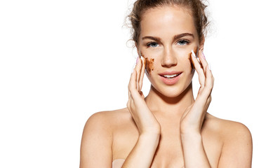 Fototapeta Portrait of charming model putting scrub on perfect skin on white background. Naturally attractive lady with shiny face. Skincare and wellness concept.