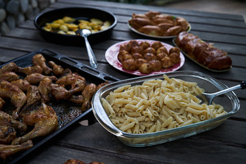 Party snack food table with baked potatoes, fried chicken drumsticks, italian pasta and puff pastry buns bread, close-up. Table with variety food top view.