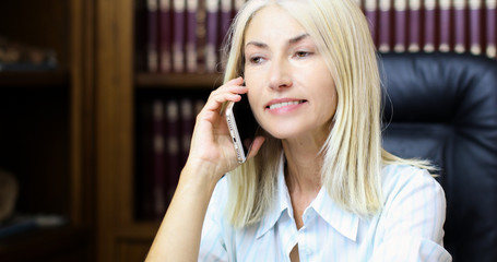 Mature secretary talking on the phone and smiling