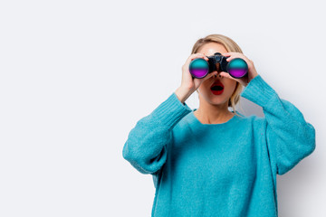 Portrait of a beautiful white woman in blue sweater with binocular on white background, isolated.
