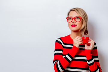 Portrait of a beautiful white smiling woman in red sweater with cup of coffee on white background, isolated.