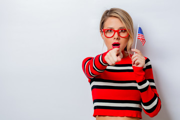 Portrait of a beautiful white woman in red sweater with USA flag on white background, isolated.