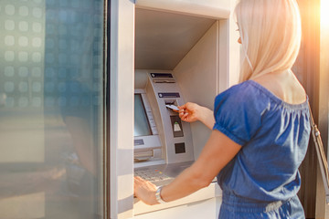 Young woman withdrawing money from credit card at ATM machine