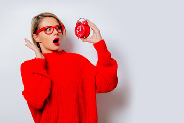 Portrait of a beautiful white woman in red sweater with little alarm clock on white background, isolated.