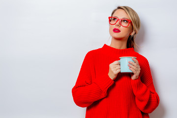Portrait of a beautiful white woman in red sweater with cup of coffee on white background, isolated.